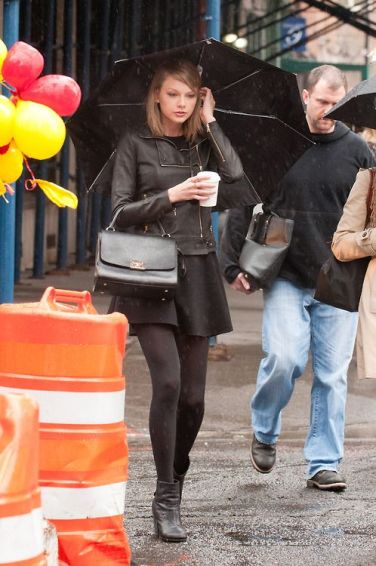 03/29/14 NYC - Taylor Swift walking in the rain with all black outfit with black mini skirt and black leather biker jacket with black umbrella and drink on hand on Saturday March 29th, 2014. Non-Exclusive / Splash News